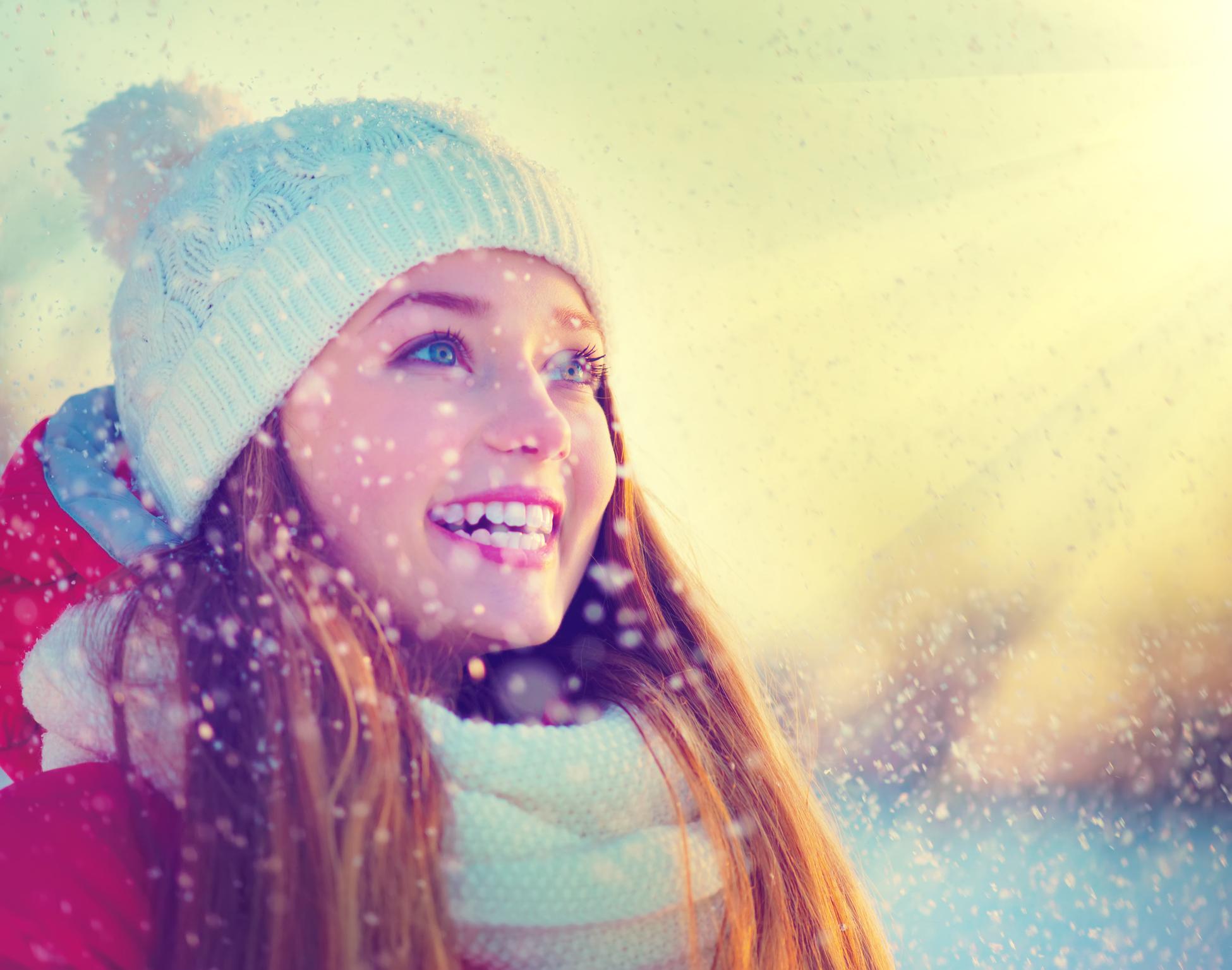 Jugendliche mit schönen Zähnen im Schnee mit Sonnenschein